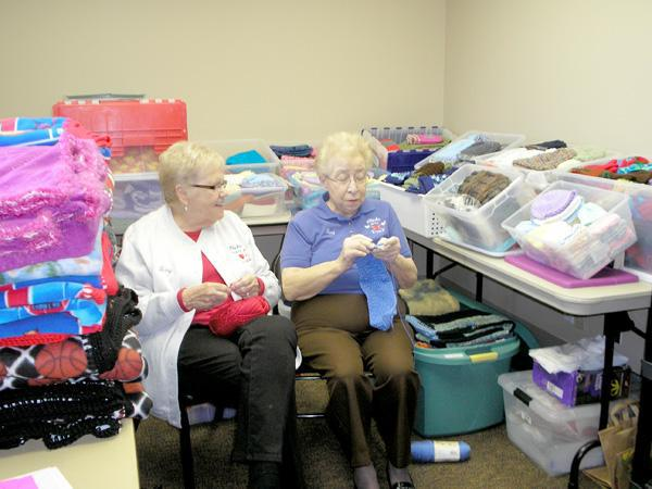 Chicks with Sticks members Terry Sands and Vera Lesinski continue their knitting projects for Friends of Foster Kids while surrounded by the efforts of the club for that organization.