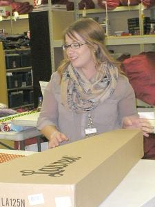 Laura Hartman, a foster care worker, said she took part of Dec. 9 off to volunteer as a wrapper for Friends of Foster Kids. Hartman said she will deliver 15 sacks of gifts to children this year. (Photo by NICOLE TUTTLE)